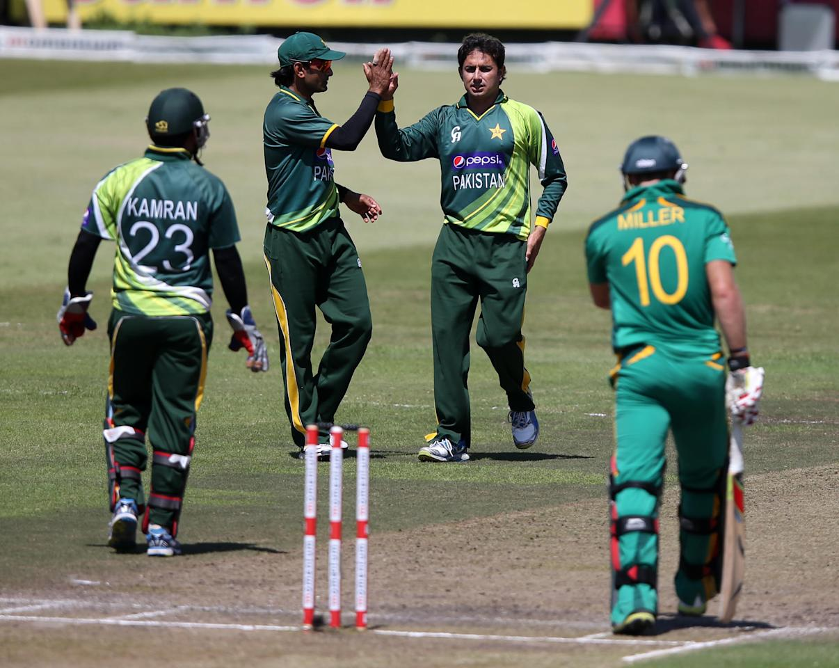 Pakistan's Saeed Ajmal (2nd R) and teammate Mohammad Hafeez celebrate the wicket of South Africa's David Miller (R) on March 21, 2013 during the fourth one-day international at Kingsmead in Durban.                  AFP PHOTO  / Stringer        (Photo credit should read -/AFP/Getty Images)