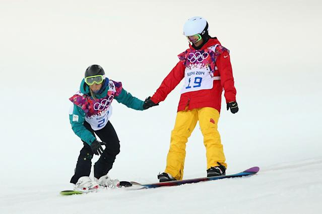 SOCHI, RUSSIA - FEBRUARY 10: Torah Bright of Australia is assisted by Xuetong Cai of China after crashing during Snowboard Halfpipe practice during day 3 of the Sochi 2014 Winter Olympics at Rosa Khutor Extreme Park on February 10, 2014 in Sochi, Russia. (Photo by Cameron Spencer/Getty Images)