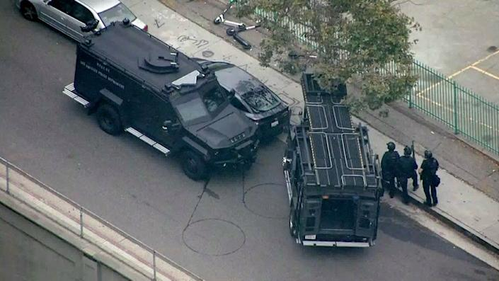 LOS ANGELES CA JULY 30, 2019 -- LAPD SWAT officers approach a Toyota Prius authorities believe was used in the possible kidnapping of a woman in Monrovia was located this morning in downtown Los Angeles with the suspect barricaded inside the car Tuesday morning, July 30, 2019. (KTLA)
