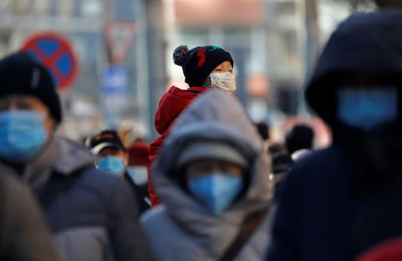 FILE PHOTO: People wearing masks walk in a street in Beijing's CBD during morning rush hour