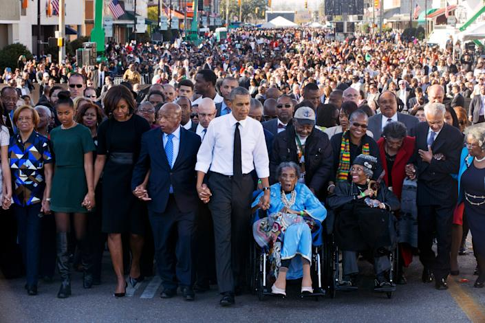 "President Barack Obama, center, walks as he holds hands with Amelia Boynton Robinson, who was beaten during ""Bloody Sunday,"" as they and the first family and others including Rep. John Lewis, D-Ga,, left of Obama, walk across the Edmund Pettus Bridge in Selma, Ala. for the 50th anniversary of ""Bloody Sunday,"" a landmark event of the civil rights movement, Saturday, March 7, 2015. From front left are Marian Robinson, Sasha Obama. first lady Michelle Obama. Obama, Boynton and Adelaide Sanford, also in wheelchair."