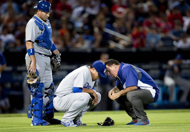 A member of the Los Angeles Dodgers training staff talks to injured starting pitcher Hyun-Jin Ryu (99) as catcher A.J. Ellis looks on at left, in the sixth inning of a baseball game against the Atlanta Braves Wednesday, Aug. 13, 2014, in Atlanta. Ryu left the game under his own power. (AP Photo/John Bazemore)
