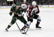 Colorado Avalanche's Cale Makar (8) keeps the puck from Minnesota Wild's Ryan Donato (6) during the second period of an NHL hockey game Sunday, Feb. 9, 2020, in St. Paul, Minn. (AP Photo/Hannah Foslien)