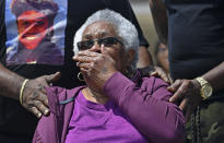 "Jessie Hamilton, seated, reacts as she is presented with a check to pay off her mortgage as LSU FIJI graduates gather to surprise their former house kitchen staff member, Saturday, April 3, 2021, and celebrate ""Jessie Hamilton Day"" in Baker, La. (Hilary Scheinuk/The Advocate via AP)"