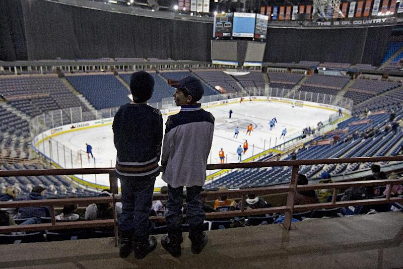 Edmonton Oilers fans Markus Taylor, left, and Thomas Hoculak watch the Edmonton Oilers take the ice during the Oilers NHL training camp in Edmonton, Alberta, on Monday Jan. 14, 2013. (AP Photo/The Canadian Press, Jason Franson)
