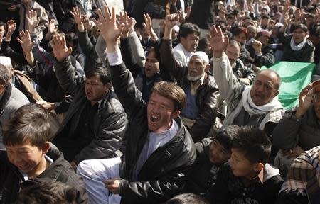 Shi'ite Muslims shout slogans beside the covered bodies of those who were killed in Tuesday night's bomb attack on a bus, during a protest in Quetta
