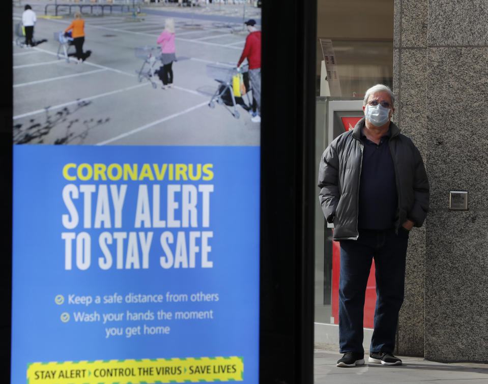 A man wearing a face mask waits on a bus stop next to a government advert with the new theme: 'Stay Alert', in London, Tuesday, May 12, 2020, as the country continues in lockdown. Britain's Prime Minister Boris Johnson announced Sunday that people could return to work if they could not work from home. (AP Photo/Frank Augstein)