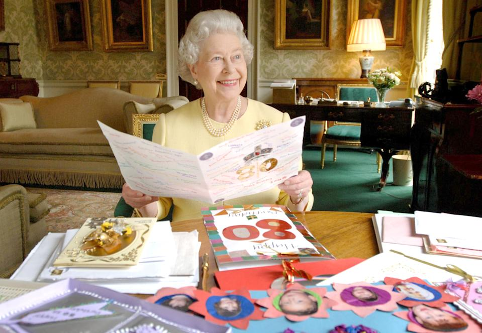 HM Queen Elizabeth II sits in the Regency Room at Buckingham Palace in London, April 20, 2006, as she looks at some of the cards which have been sent to her for her 80th birthday. (Photo by Anwar Hussein Collection/ROTA/WireImage)
