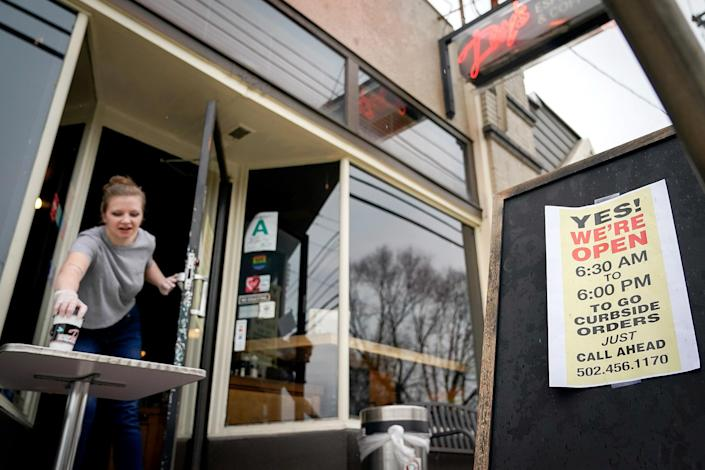Image: Kayla Marx places an order outside the door of Day's Espresso and Coffee Shop after a state mandated carry-out only policy went into effect in order to slow the spread of the novel coronavirus (COVID-19) in Louisville (Bryan Woolston / Reuters)
