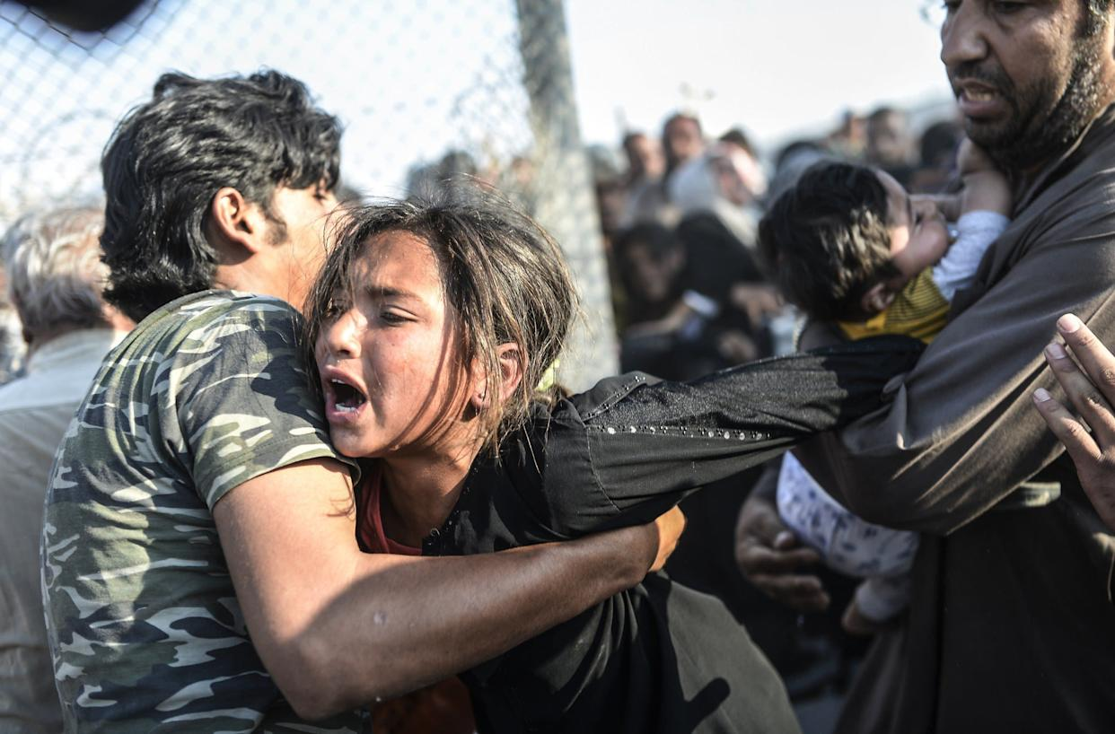 Syrians fleeing the war rush through broken down border fences to enter Turkish territory illegally, near the Turkish border crossing at Akcakale in Sanliurfa province on June 14, 2015.