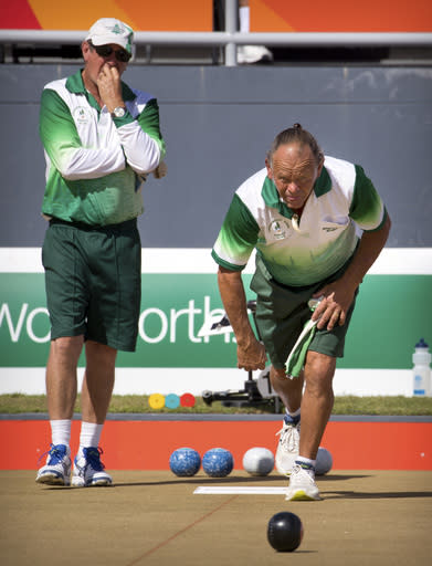Second Hadyn Evans of Norfolk Island, right, bowls as lead Philip Jones watches during their men's triples semifinal lawn bowling match against Scotland at the Broadbeach Bowls Club during the 2018 Commonwealth Games on the Gold Coast, Australia, Sunday, April 8, 2018. The Norfolk team won the bronze medal with a 19-16 victory over Canada, securing the islands second medal ever at the Commonwealth Games.(AP Photo/Mark Schiefelbein)