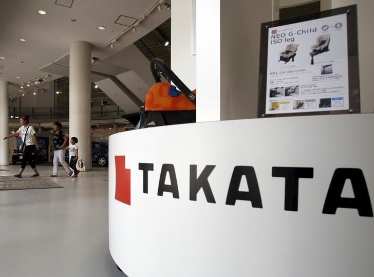 Visitors walk behind a logo of Takata Corp on its display at a showroom for vehicles in Tokyo