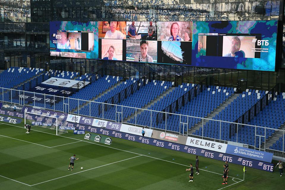 Screens showing supporters watching a live broadcast of the 2019/20 Russian Football Premier League match between Dynamo Moscow and CSKA Moscow at VTB Arena.