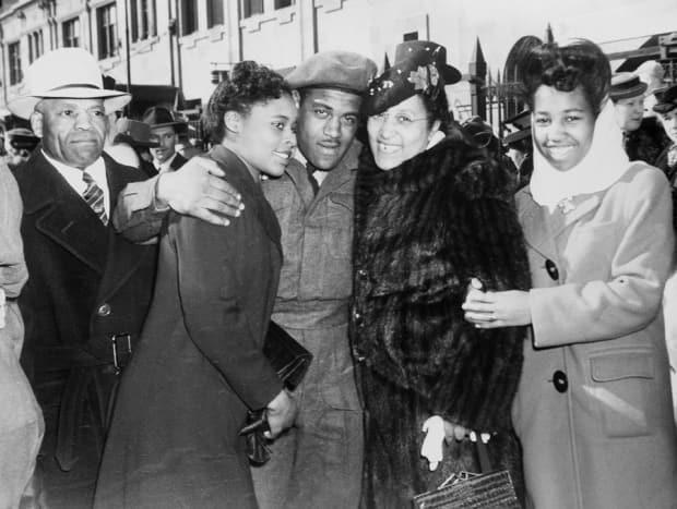 Violet King, right, stands beside her family as her brother, Ted, arrives back in Calgary in 1946.