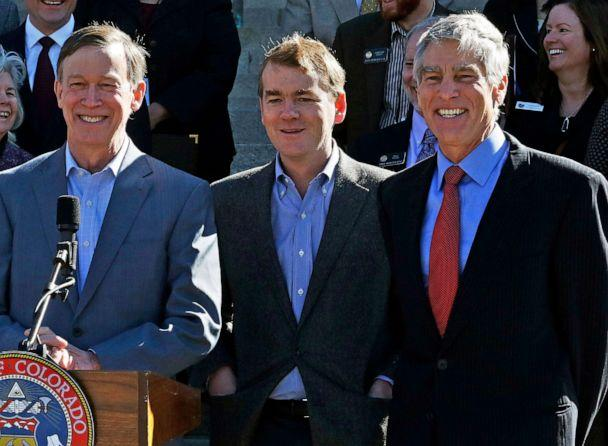 PHOTO: Senators Mark Udall, right, and Michael Bennet, center, stand with Colo. Gov. John Hickenlooper, during an event on the front steps of the state Capitol in Denver, March 14, 2014. (Brennan Linsley/AP, FILE)