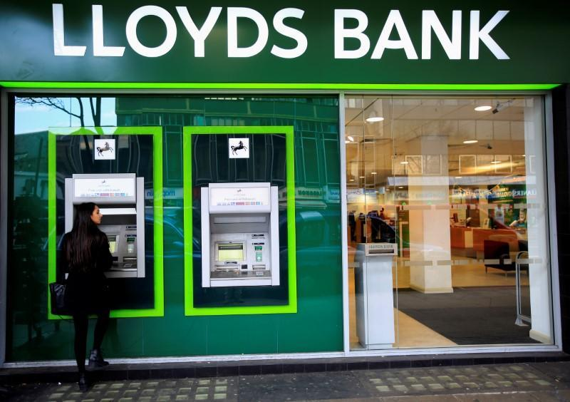 FILE PHOTO: A woman uses a cash machine at a Lloyds Bank branch in central London
