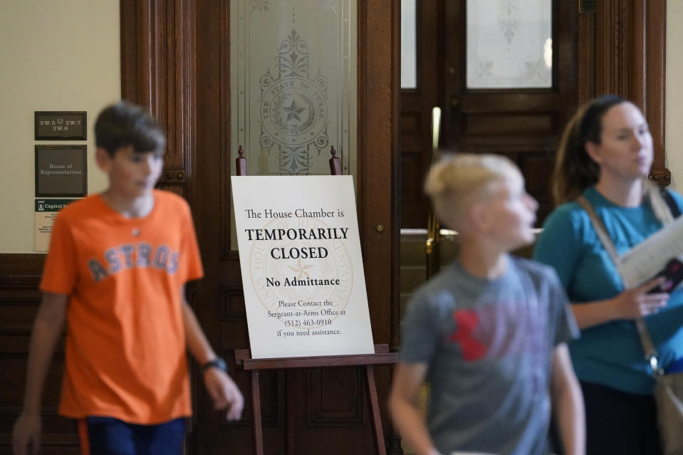 """Visitors walk past the """"Temporarily Closed"""" doors to the House Chamber at the State Capitol, Tuesday, June 1, 2021, in Austin, Texas. The Texas Legislature closed out its regular session Monday, but are expected to return for a special session after Texas Democrats blocked one of the nation's most restrictive new voting laws with a walkout. (AP Photo/Eric Gay)"""
