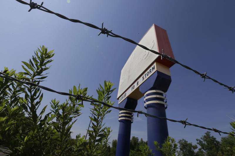 An entrance sign to the former Six Flags Amusement Park is seen in New Orleans, Wednesday, Aug. 28, 2013. The park closed for Hurricane Katrina and never reopened. Thursday is the eighth anniversary of Hurricane Katrina. (AP Photo/Gerald Herbert)