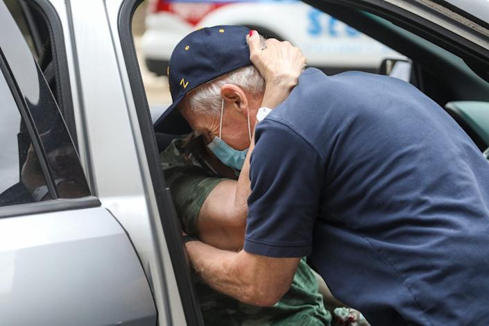 """Deanna Hair embraces her husband Ken Hair as he whispers """"You made it"""" placing her in the car after being discharged from the University of Michigan hospital battling COVID-19 for 196 days on Oct. 15, 2020."""