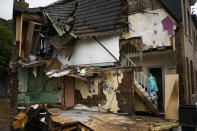 A woman walks up the stairs in her damaged house after flooding in Ensival, Vervier, Belgium, Friday July 16, 2021. Severe flooding in Germany and Belgium has turned streams and streets into raging torrents that have swept away cars and caused houses to collapse. (AP Photo/Francisco Seco)