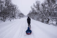 A man pulls a child on a sleigh, during a heavy snowfall in Bustarviejo, outskirts of Madrid, Spain, Saturday, Jan. 9, 2021. A persistent blizzard has blanketed large parts of Spain with 50-year record levels of snow, halting traffic and leaving thousands trapped in cars or in train stations and airports that suspended all services as the snow kept falling on Saturday. Half of Spain is on alert, with five provinces on their highest level of warning. (AP Photo/Bernat Armangue)
