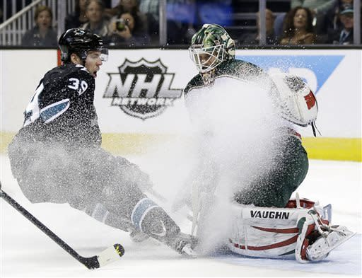 San Jose Sharks center Logan Couture (39) kicks up ice with his skates as he closes in on Minnesota Wild goalie Niklas Backstrom, of Finland, during the first period of an NHL hockey game in San Jose, Calif., Thursday, April 18, 2013. (AP Photo/Marcio Jose Sanchez)