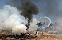 A Palestinian protester uses a slingshot to return a tear gas canister toward Israeli security forces during clashes following a demonstration against settlements in the village of Beita in the occupied West Bank, on October 8 (AFP/Jaafar ASHTIYEH)