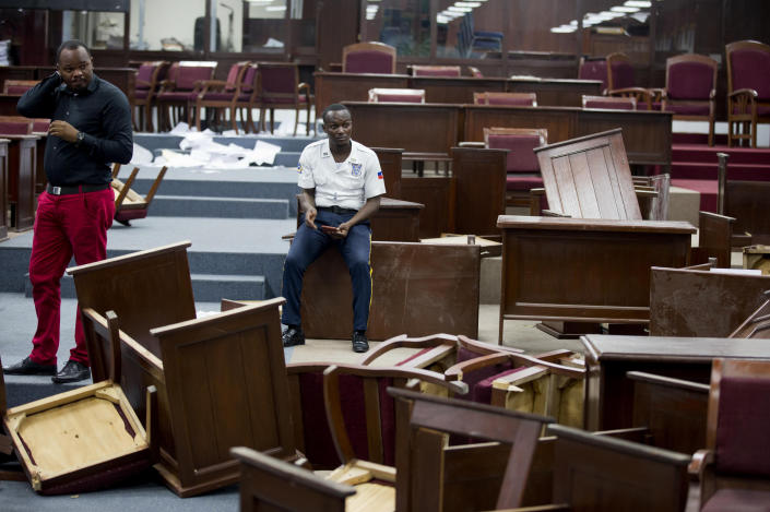 FILE - In this Sept. 3, 2019 file photo, a security officer sits amid overturned tables inside Parliament after it was vandalized in Port-au-Prince, Haiti. Opposition lawmakers turned desks over in the Chamber of Deputies, hours before the planned ratification of Prime Minister Fritz William Michel. The vote was indefinitely postponed. (AP Photo/Dieu Nalio Chery, File)