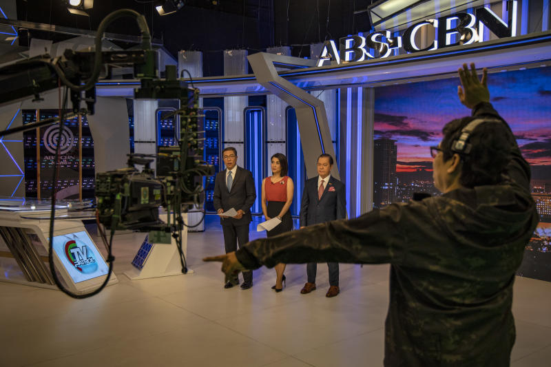 """FILE PHOTO: The floor director gestures to anchors on the set for """"TV Patrol"""", ABS-CBN's flagship news program, on February 11, 2020 in Quezon City, Metro Manila, Philippines. (Photo by Ezra Acayan/Getty Images)"""