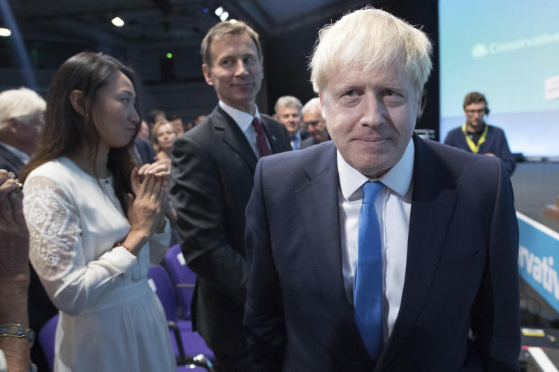 "Boris Johnson walks to the stage, as rival Jeremy Hunt looks on after the announcement of the result in the ballot for the new Conservative party leader, in London, Tuesday, July 23, 2019. Brexit hardliner Boris Johnson won the contest to lead Britain's governing Conservative Party on Tuesday and will become the country's next prime minister, tasked with fulfilling his promise to lead the U.K. out of the European Union ""come what may."" (Stefan Rousseau/Pool photo via AP)"