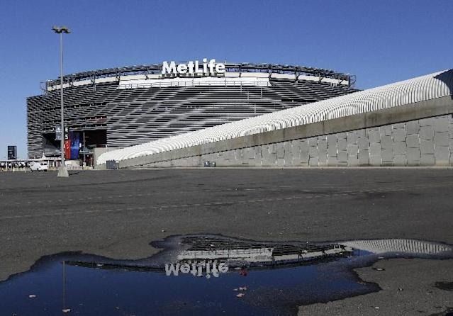 """In this photo taken Wednesday, Nov. 13, 2013, MetLife Stadium is reflected on a puddle on the stadium's parking lot in East Rutherford, N.J. Northern New Jersey towns hoping to get Super Bowl visitors to spend time and money in the Garden State and not just across the river in Manhattan, realize they need to come up with a creative game plan to separate itself from New York. There's a catch: None of the festivities can employ the words """"Super Bowl,"""" a name that is trademarked by the NFL. (AP Photo/Julio Cortez)"""
