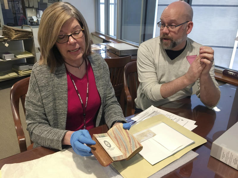 In this Feb. 14, 2018 photo, India Spartz, left, head of special collections and archives at Union College, and librarian John Myers look at an old almanac from the college archives in Schenectady, N.Y. The almanac was found to contain a lock of George Washington's hair that had been a gift to James A. Hamilton in 1871. (AP Photo/Mary Esch)