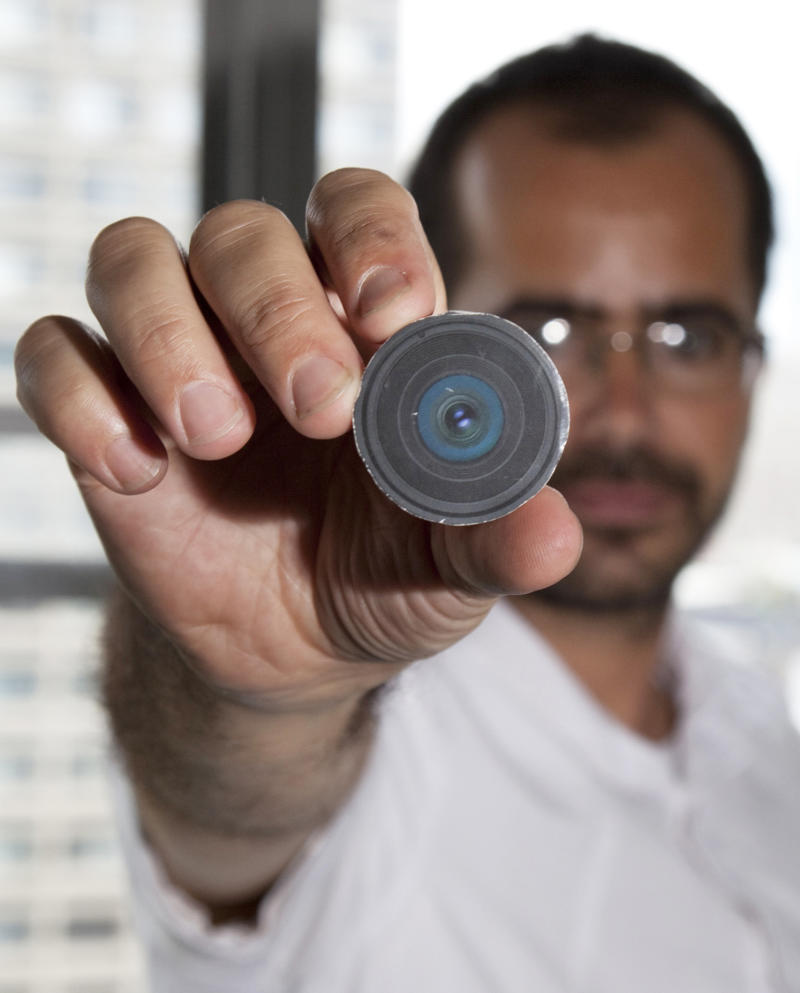 """This Aug. 24, 2010 photo provided by New York University arts professor Wafaa Bilal, shows Bilal holding the prototype of a digital camera that he had implanted in the back of his head, in New York.  Bilal, a visual artist widely recognized for his interactive and performance pieces, has undergone surgery to implant a tiny camera in the back of his head for an artwork commissioned by a new museum in Doha, Qatar. Titled """"The 3rd I,"""" it is one of 23 contemporary works commissioned for the opening of Mathaf: Arab Museum of Modern Art on Dec. 30, 2010. (AP Photo/Wafaa Bila, Bard Farwell) NO SALES"""