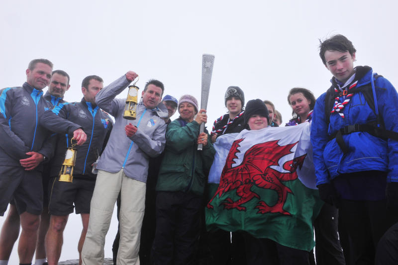 In this image issued by LOCOG shows the Paralympic Flame being held to the summit of Mount Snowdon in Wales, accompanied by LOCOG Chairman Sebastian Coe, 4th left, after groups of disabled and non-disabled Scouts from Gwynedd Scouts, used the traditional technique of rubbing flint together to create the flame that will light the Paralympic Torch, Wednesday Aug. 22, 2012. The London Paralympic Games open on Wednesday Aug. 29. (AP Photo/Ben Birchall/LOCOG)