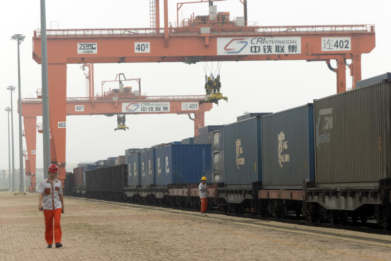 In this July 25, 2019, photo, a worker walks past a cargo train bound for Europe at a train station in Dalian in northeastern China's Liaoning Province. Authorities in China's rust-belt region are looking for support for its revival from Beijing's multibillion-dollar initiative to build ports, railways and other projects abroad. (AP Photo/Olivia Zhang)
