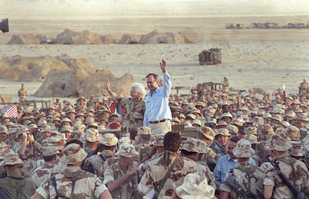 President George Bush and Barbara Bush with U.S. and British troops after a Thanksgiving Day visit in the Saudi desert in 1990. (Photo: Rick Wilking/Reuters)
