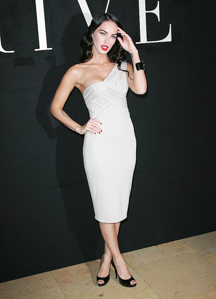 "Megan Fox arrived at the Armani Prive show during Paris Fashion Week in a dove gray dress from the designer's latest collection. The ""Transformers"" tart paired the one-shouldered sheath with black peep toes, a cuff, and ruby red lipstick. Tony Barson/<a href=""http://www.wireimage.com"" target=""new"">WireImage.com</a> - July 7, 2009"