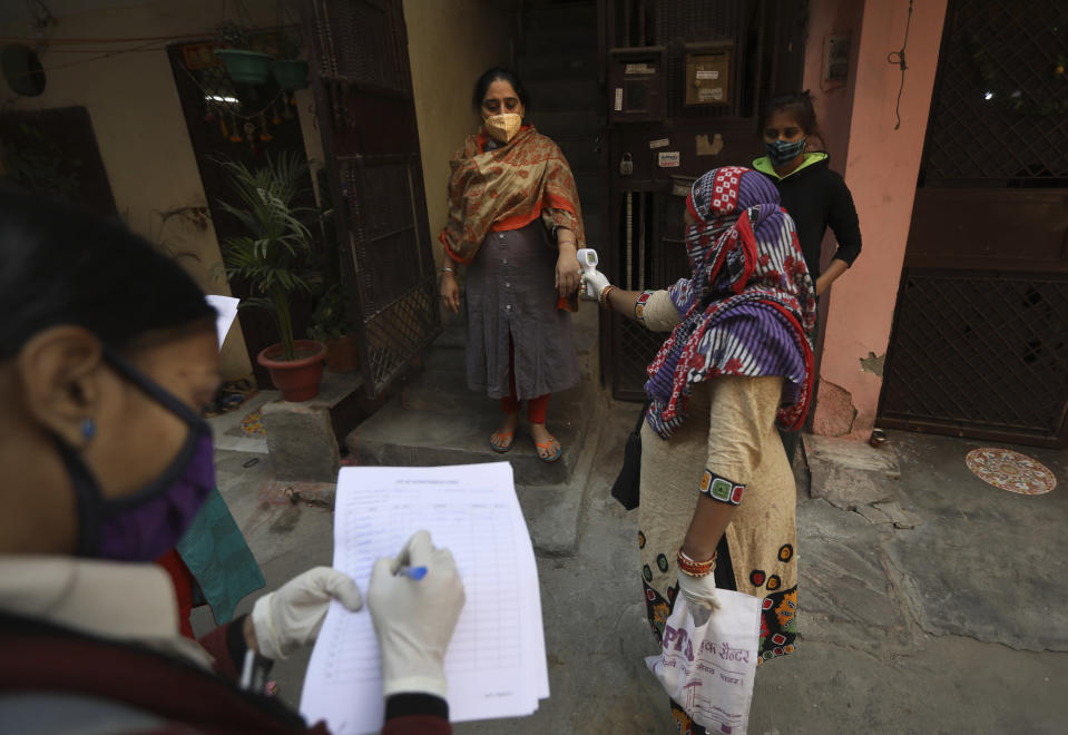 A health worker reads the temperature of a woman during a door to door survey to assess the COVID-19 situation in New Delhi, India, Monday, Nov. 23, 2020. India has more than 9 million cases of coronavirus, second behind the United States. (AP Photo/Manish Swarup)