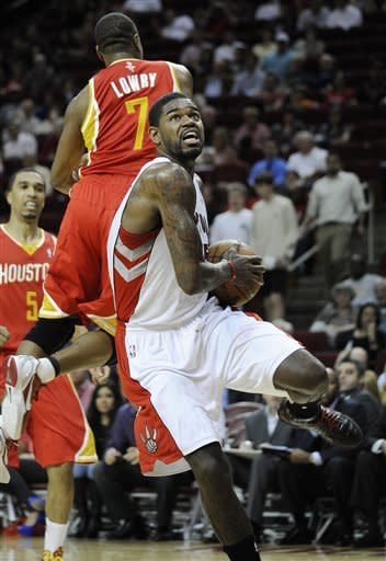 Toronto Raptors' Amir Johnson, front, heads to the basket after getting past Houston Rockets' Kyle Lowry (7) in the first half of an NBA basketball game Tuesday, Feb. 28, 2012, in Houston. (AP Photo/Pat Sullivan)