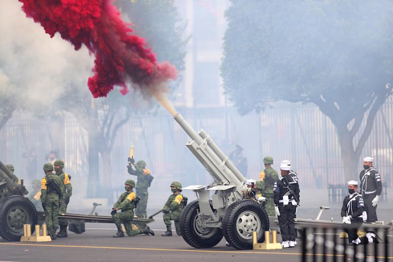 VARIOUS CITIES, MEXICO - SEPTEMBER 16: Soldiers fire a ceremonial artillery salute during the Independence Day military parade at Zocalo Square on September 16, 2020 in Various Cities, Mexico. This year El Zocalo remains closed for general public due to coronavirus restrictions. Every September 16 Mexico celebrates the beginning of the revolution uprising of 1810. (Photo by Hector Vivas/Getty Images)