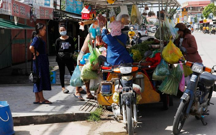 Customers buy some foods from a motor-cart's mobile market during lockdown, - Heng Sinith/AP