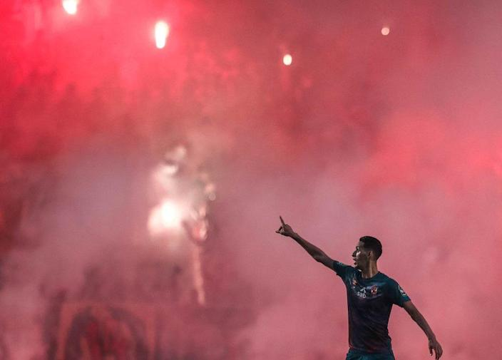 A footballer in front of a red mist in the Olympic Stadium in Rades, Tunisia - Saturday 19 June 2021