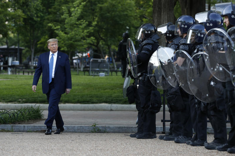 FILE - In this Monday, June 1, 2020, file photo President Donald Trump walks past police in Lafayette Park after visiting outside St. John's Church across from the White House in Washington. The violent clearing of demonstrators from the nation's premier protest space in front of the White House is spotlighting a tiny federal watch force created by George Washington. Democratic lawmakers want answers about the clubbing, punching and other force deployed by some Park Police in routing protesters from the front of the White House on Monday, (AP Photo/Patrick Semansky, File)