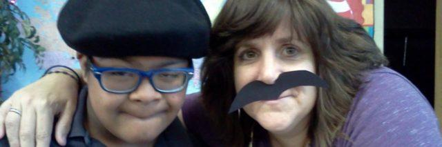 Selfie of child with a disability and teacher. Teacher is wearing a fake mustache.