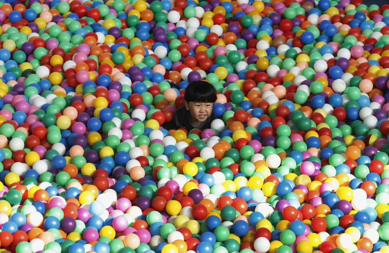 A boy plays in a ball pit at an indoor playground for children at a wealthy district in Beijing March 31, 2013. The entry fee for this indoor playground is RMB 50 ($8) per child for three hours. China has pledged to double household incomes over the coming decade in a bid to close a wealth gap so wide it threatens social stability. Although the proportion of extreme poverty has fallen over recent decades, about 12 percent of the country's 1.3 billion people still live on less than $1.25 per day, according to a 2013 United Nations report. Picture taken on March 31, 2013. REUTERS/Kim Kyung-Hoon (CHINA - Tags: BUSINESS SOCIETY WEALTH)