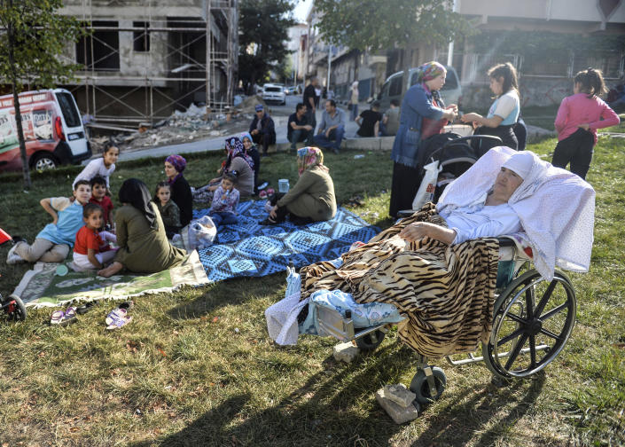People sit in a grassy area after evacuating their homes, following an earthquake in Istanbul, Thursday, Sept. 26, 2019. Turkey's emergency authority says a 5,8 magnitude earthquake has shaken Istanbul with no immediate damage reported. Official Anadolu news agency, quoting the Istanbul governor's office, said there were no reports of damage. Experts have warned a major earthquake is expected to hit Istanbul, Turkey's most populous city with more than 15 million residents. (Ibrahim Mase/DHA via AP)