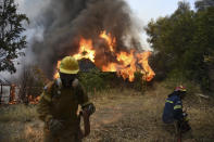 Firefighters operate during a wildfire near Lampiri village, west of Patras, Greece, Saturday, Jul. 31, 2021. The fire, which started high up on a mountain slope, has moved dangerously close to seaside towns and the Fire Service has send a boat to help in a possible evacuation of people. (AP Photo/Andreas Alexopoulos)