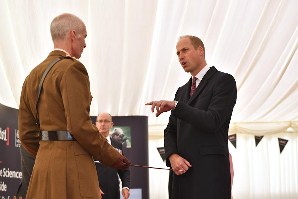 SALISBURY, ENGLAND - OCTOBER 15: Prince William, Duke of Cambridge, (R) presents British Army Colonel Mike Duff (L), Assistant Commander South West and deputy joint commander for the decontamination of Salisbury following the 2018 Novichok incident, with the Firmin Sword of Peace for the South West department's work on the Novichok incident, during the Duke's visit to the Defence Science and Technology Laboratory (Dstl) at Porton Down science park on October 15, 2020 near Salisbury, England. The Queen and the Duke of Cambridge visited the Defence Science and Technology Laboratory (Dstl) where they were to view displays of weaponry and tactics used in counter intelligence, a demonstration of a Forensic Explosives Investigation and meet staff who were involved in the Salisbury Novichok incident. Her Majesty and His Royal Highness also formally opened the new Energetics Analysis Centre. (Photo by Ben Stansall - WPA Pool/Getty Images)