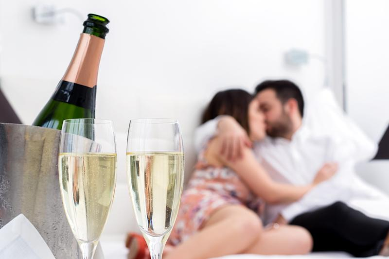 Close up Champagne glasses and cold bottle in ice bucket with kissing couple in background.