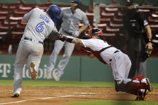 Boston Red Sox's Christian Vazquez tags out Toronto Blue Jays' Travis Shaw (6) at home plate during the sixth inning of a baseball game, Saturday, Aug. 8, 2020, in Boston. (AP Photo/Michael Dwyer)